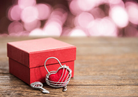 nostalgy: Key with the heart and gift box as a symbol of love with red heart on grunge old background