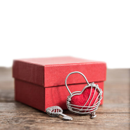 Key with the heart and gift box as a symbol of love with red heart on grunge old background photo