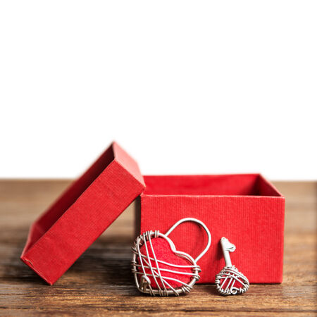open giftbox and Key with the heart as a symbol of love on wood table on white background photo
