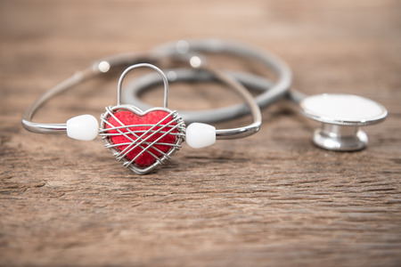 Red heart and a stethoscope on wood background photo