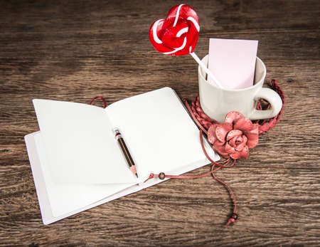 greeting card for Valentines Day , with red heart symbol of candy with coffee cup and paper note on wood background photo
