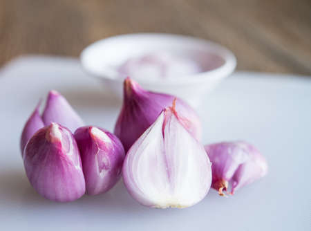 red onions: Red onions on a plastic chopping board