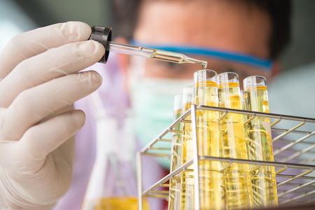 科学研究室で実験用ガラス試験管に黄色の液体の滴と研究室のピペット。男を着てゴーグル 写真素材
