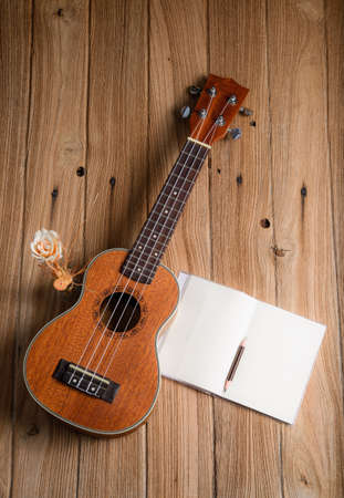 acoustic ukulele: ukulele with notebook on wood background