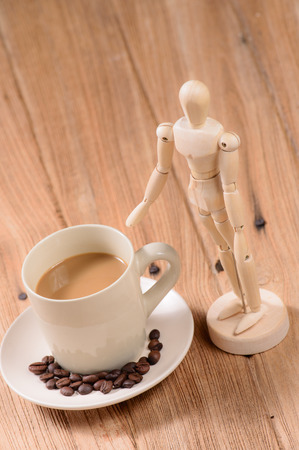 marioneta de madera: cup of coffee with wooden puppet on wood background Foto de archivo