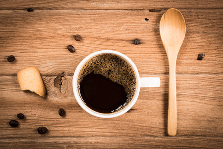 Coffee cup and cookie on a wooden table. photo
