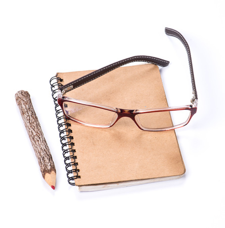 color pencil made of branches with glasses and notebook on white background photo