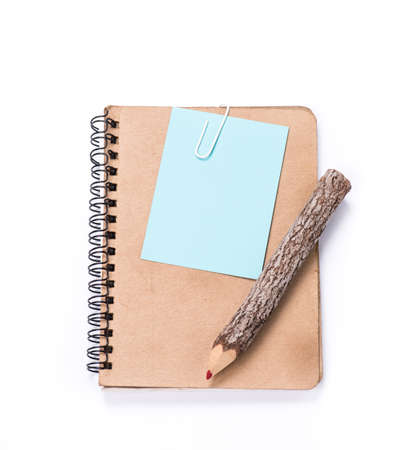 brown notebook and a pencil on white background photo