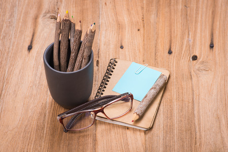 color pencil made of branches in cup with glasses and note book on wood background photo