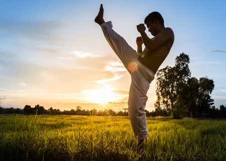 man training karate on sunset.
