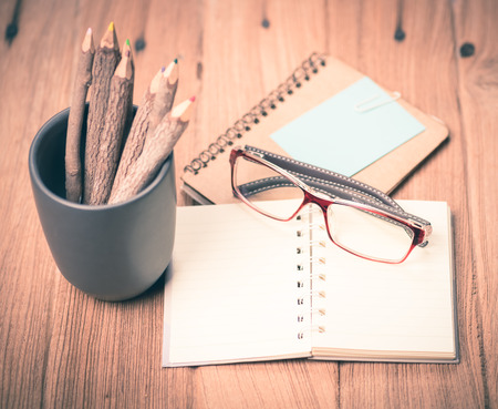 color pencil made of branches with glasses and note book on wood background,vintage tone style photo