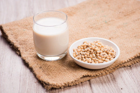 Soybeans and soy milk in a glass. 写真素材