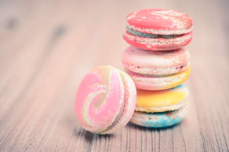 A lot of french colorful macarons on a woody floor in vintage tone style photo