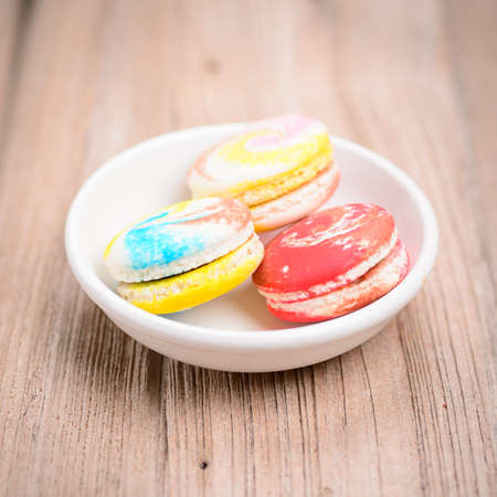 A lot of french colorful macarons The plate on wood background photo