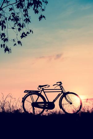 mooi landschapsbeeld met Silhouetfiets bij zonsondergang in uitstekende toonstijl Stockfoto