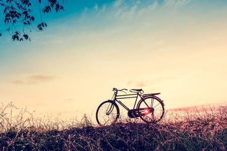 ビンテージ トーン スタイルの夕日シルエット自転車と美しい風景の画像
