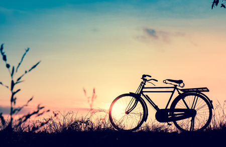 image: beautiful landscape image with Silhouette  Bicycle at sunset in vintage tone style