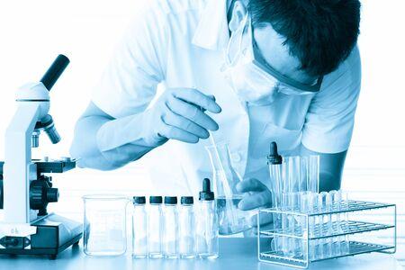 laboratorio clinico: Investigador de sexo masculino médico o científico o médico de hombre mirando un tubo de ensayo de solución clara en un laboratorio con microscopio lado de los hombres; efecto de tono cyanotype