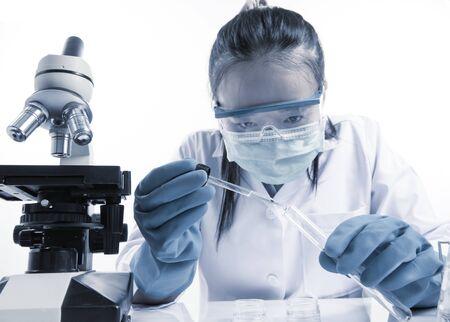 laboratorio clinico: investigador médico o científico o mujer médico mirando un tubo de ensayo de solución clara en un laboratorio con su microscopio a su lado; efecto de tono cyanotype Foto de archivo