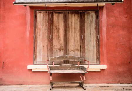 window bench: sidewalk scene with wooden vintage bench and red wall with wood window Stock Photo