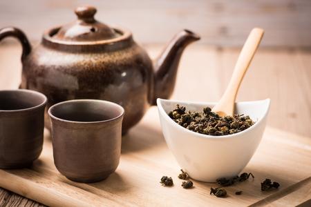 dry tea leaf in ceramic bowl wit pot on wood background