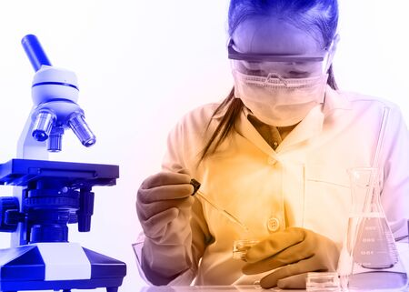 surgical coat: female medical or scientific researcher or woman doctor looking at a test tube of clear solution in a laboratory with her microscope beside her