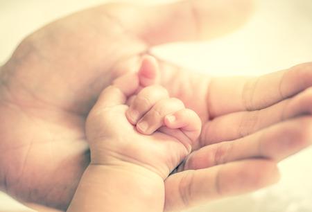 빈티지 여과 스타일로 아기의 손을 잡고 아버지