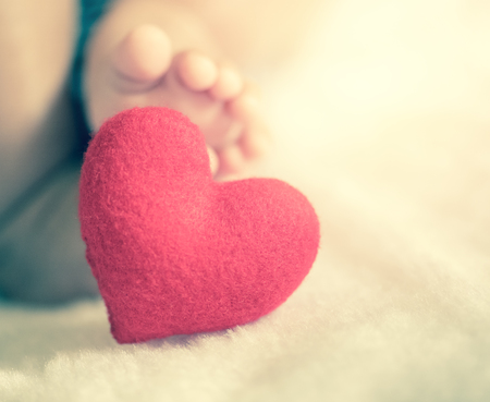 gentleness: babys feet with a red heart in vintage filtered style
