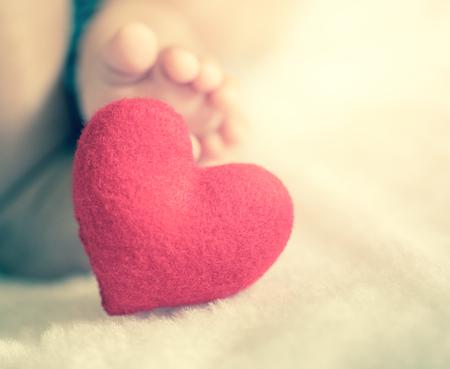 primeros auxilios: los pies del bebé con un corazón rojo en el estilo filtrada vendimia