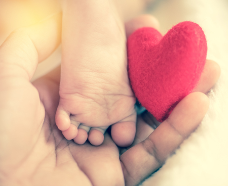 baby's feet: babys feet with a red heart in vintage filtered style