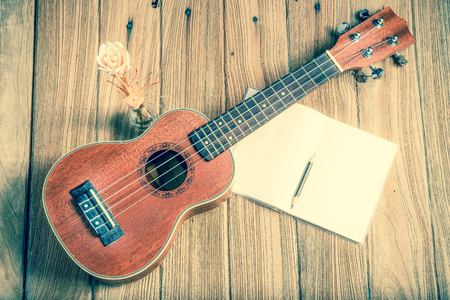 acoustic ukulele: ukulele with notebook on wood background : vintage filtered tone style Stock Photo