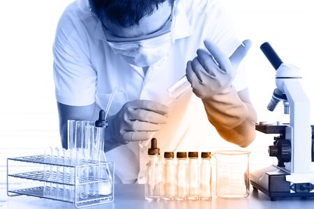 clinical research: male medical or scientific researcher or man doctor looking at a test tube of clear solution in a laboratory with microscope beside men Stock Photo
