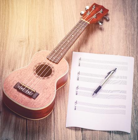 ukelele: Ukulele and musical paper notes. vintage tone style