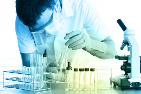 surgical coat: male medical or scientific researcher or man doctor looking at a test tube of clear solution in a laboratory with microscope beside men Stock Photo