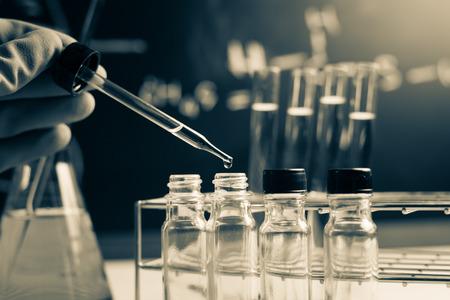 investigando: La investigaci�n de laboratorio, cayendo l�quido qu�mico a tubos de ensayo Foto de archivo