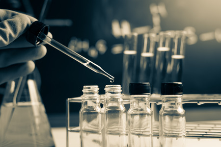 Laboratory research, dropping chemical liquid to test tubes Stock Photo