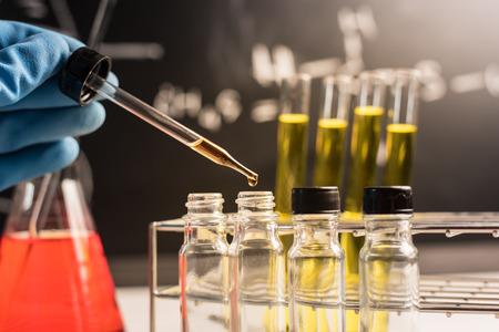 investigando: La investigación de laboratorio, cayendo líquido químico a tubos de ensayo Foto de archivo