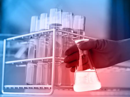 trabajador petroleros: Frasco de científico mano con el tubo de ensayo en el bastidor