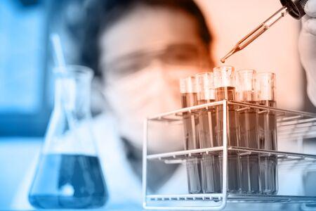 equipos medicos: Tubos de ensayo químico de laboratorio de cristal con liquid.Man lleva gafas protectoras