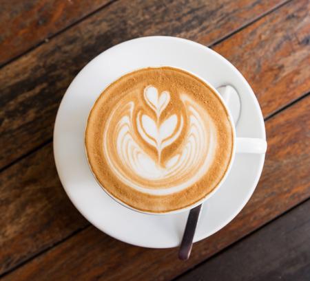 Um copo do café quente latte art na tabela de madeira