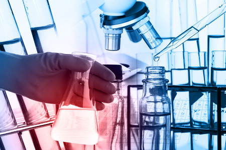 chemistry science: Conical flask in scientist hand with lab glassware background, Laboratory research concept