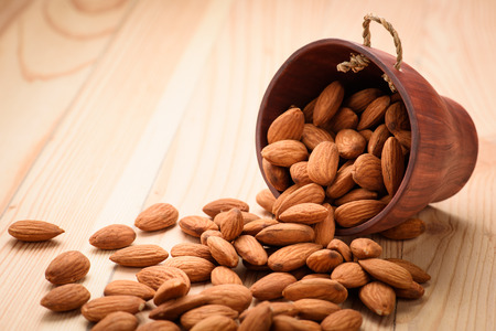 almond: Almonds pour from wood Cup