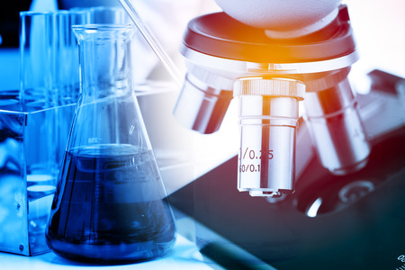 health care research: Laboratory research, flask containing chemical liquid with microscope Stock Photo