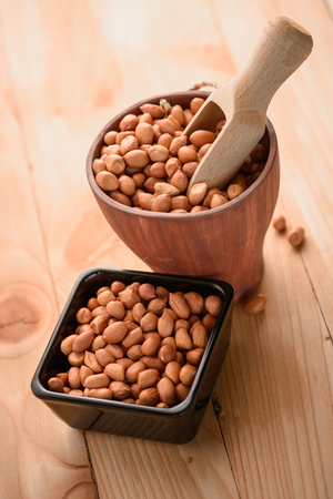 monkey nuts: Raw peanuts or arachis in ceramic bowl