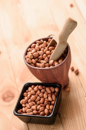 arachis: Raw peanuts or arachis in ceramic bowl