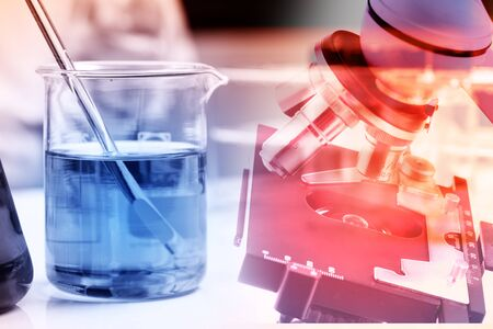 Laboratory research, flask containing chemical liquid with microscope Stock Photo