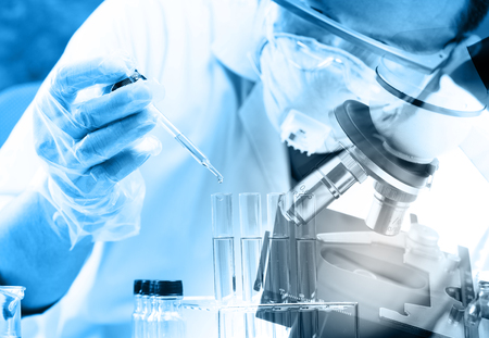 investigador cientifico: cient�fico cayendo l�quido qu�mico al matraz con fondo de la cristaler�a de laboratorio, el concepto de investigaci�n de laboratorio Foto de archivo