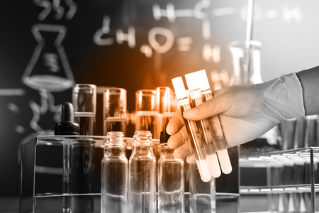 Flask in scientist hand with lab equipment background