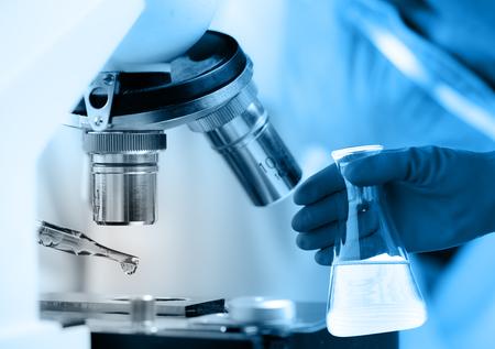microscopio: Científico cayendo líquido químico al microscopio, el concepto de investigación de laboratorio
