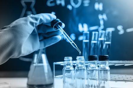 industria quimica: La investigaci�n de laboratorio, cayendo l�quido qu�mico a tubos de ensayo Foto de archivo